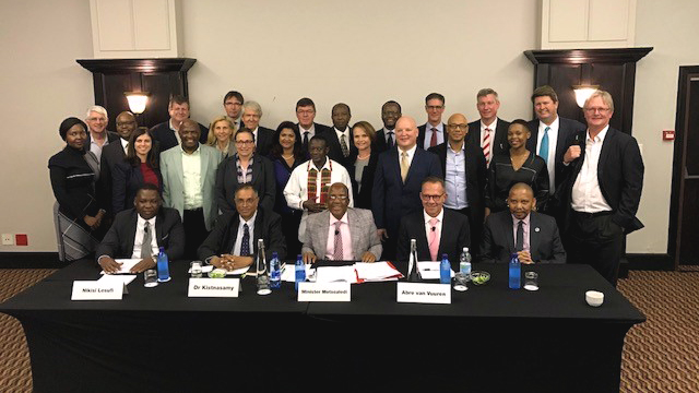 Attorney Mike Elsner (back, second from right) with co-counsel Richard Spoor (far right), South African Minister of Health Aaron Motsoaledi (center seat), Gold Mine Company Officers and Directors and respondents' lawyers after signing the historic settlement agreement for South African gold workers' class action today in Johannesburg.